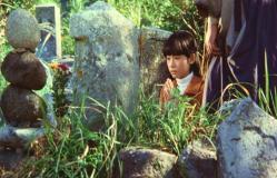 墓に手を合わせる美禰子(みねこ)
