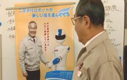 ホワイトボードにポスターを貼る木村電気社長