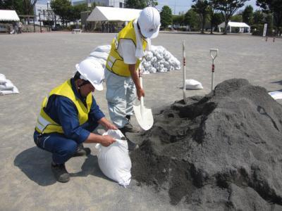 スコップで袋に砂を入れる