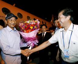 中国政府のチャーター機で福建省福州市の空港に到着し、歓迎を受けるセン其雄船長(左)=25日未明(新華社=共同)