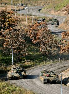 %演習で進む90式戦車(手前)=17日午前8時48分、大分県の日出生台演習場