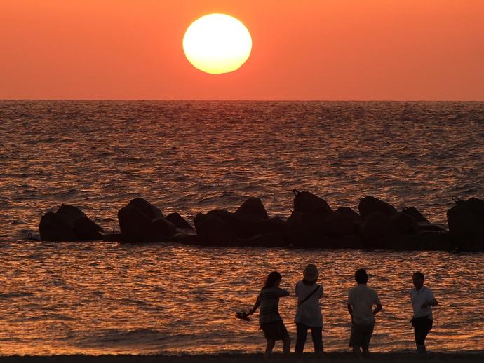 白山市徳光海岸の夕日 真ん丸夕日とはしゃぐ若者