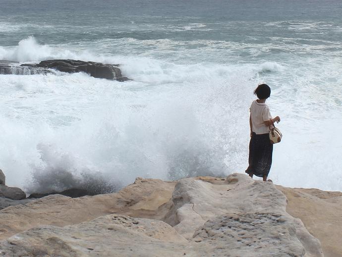 千畳敷に打ち寄せる波と女性