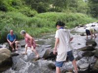 子供のように水遊びする先生夫婦とJ子さんと魚の罠を仕掛けている息子