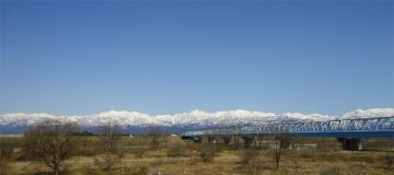 橋と残雪の山並み