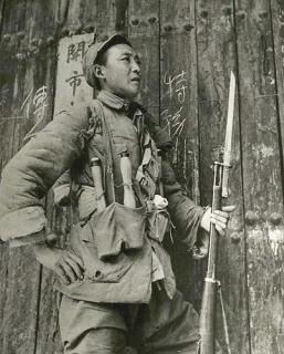 a Victorious chinese soldier posing with his rifle after the battle of Taierzhuang in 1938