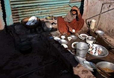 家の外で皿を洗う老女