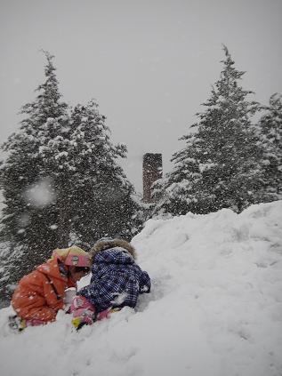 家の前の雪山で遊ぶ二人