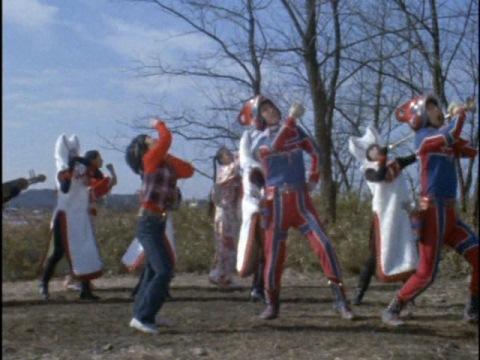 ファイル星人達も一緒に、山本リンダの『狙いうち』を歌う東隊員