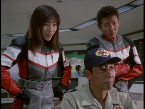 訓練所で成績優秀者のデータを見るユミムラ・リョウ隊員(演:斉藤りさ)