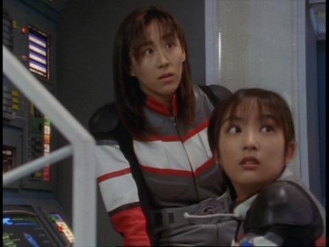バオーンの名前を聞き、ヒビキ隊長の方を見るユミムラ・リョウ隊員(演:斉藤りさ)