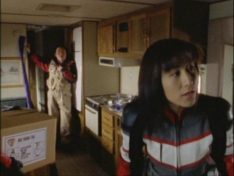 ナカジマ隊員の陣中見舞いに来て、部屋の中を見回すユミムラ・リョウ隊員(演:斉藤りさ)