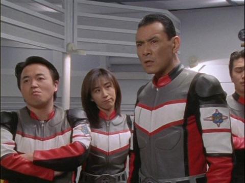 アスカ隊員が連絡が取れないと隊長に告げるユミムラ・リョウ隊員(演:斉藤りさ)