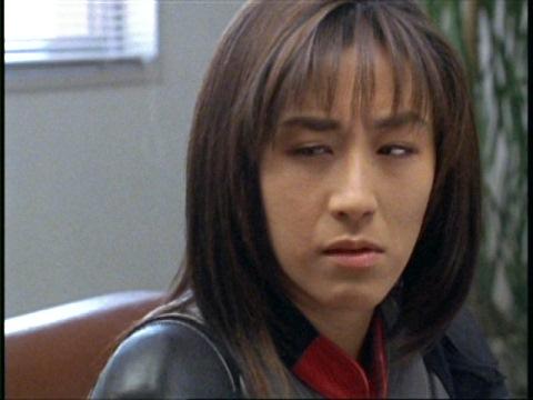 女子高生に鼻の下を伸ばすアスカ隊員に蹴りを入れるユミムラ・リョウ隊員(演:斉藤りさ)
