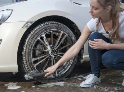 タイヤを洗車する女性
